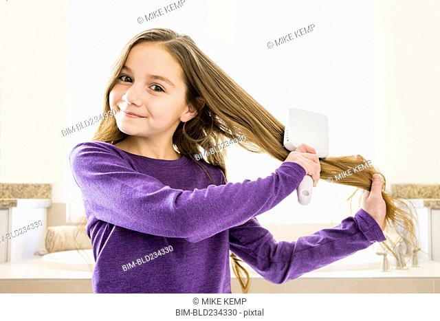 Caucasian girl brushing hair in bathroom
