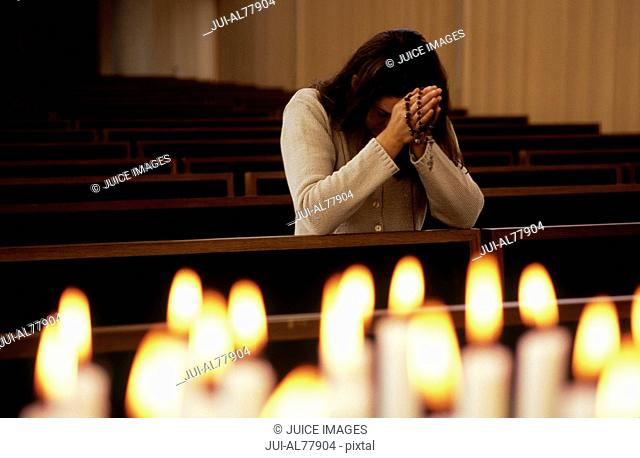 Close up of candles lit with woman praying in church