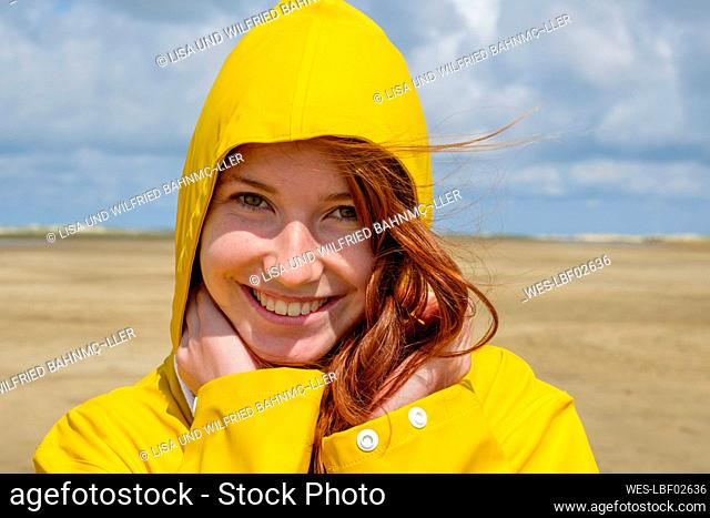 Close-up portrait of redhead teenage girl wearing yellow raincoat while standing at beach against sky on sunny day