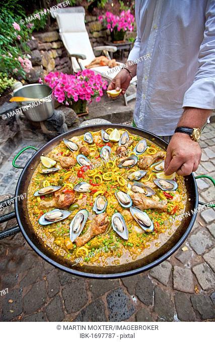 Cook preparing a paella, a Spanish rice dish, adding lemon, series, no. 6