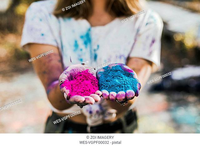 Girl holding Holi powder colours, Germany