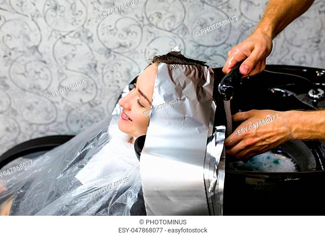 girl wash her head in a beauty salon. Hair dying coloring, foil