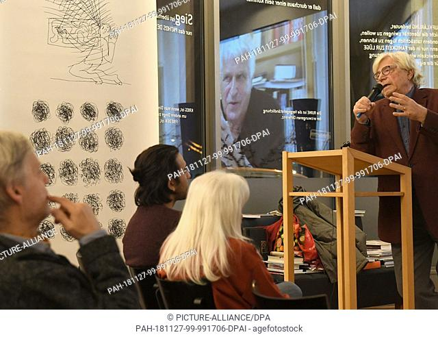 27 November 2018, Berlin: The artist and art theorist Bazon Brock (r) speaks at an exhibition of the artist Fridhelm Klein (m, in the projection) in Denkerei