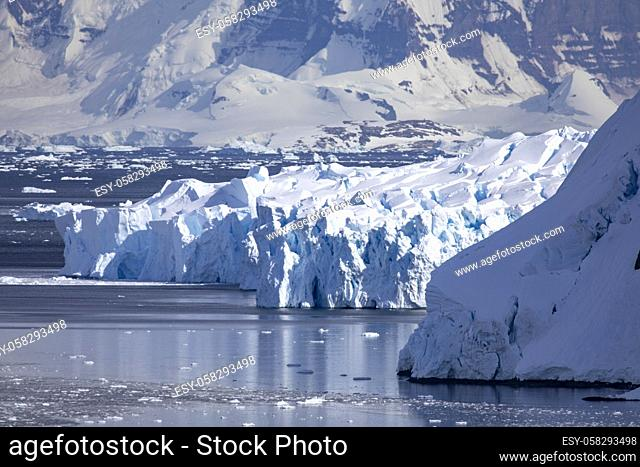 Cool bluish ice from glacier flows into sea in bay with mountains in Antarctica