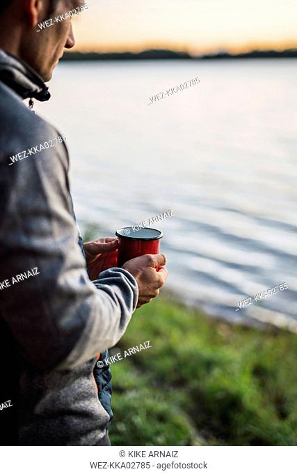 Man looking at the lake, drinking coffee