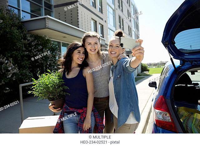 College students taking selfie moving into college dorm