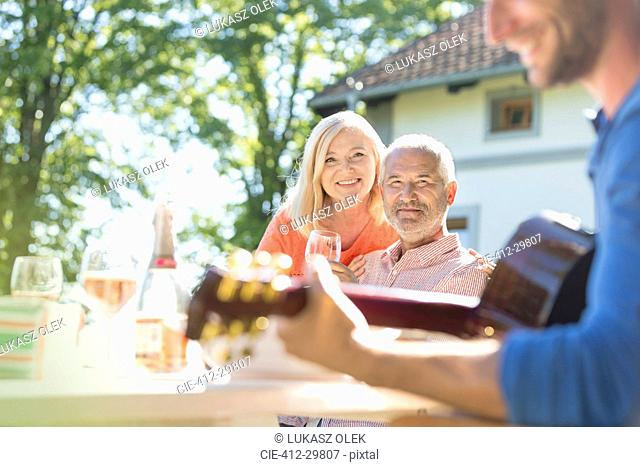 Senior couple drinking wine and watching adult son playing guitar on sunny patio