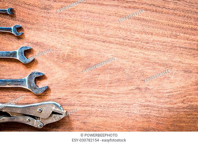 Wrench and locking pliers row on wooden pattern copy space background