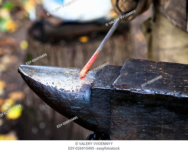 red hot iron rod on anvil in outdoor rural smithy