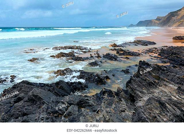 Storm on Castelejo beach with black schist cliffs (Algarve, Portugal). All people are unrecognizable