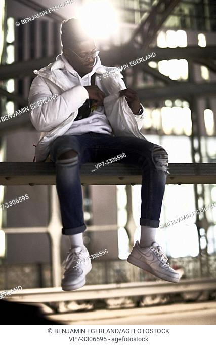 young African man sitting on metal construction of bridge, Hackerbrücke, Hacker bridge, in city at night, checking inside pocket of jacket, in Munich, Germany