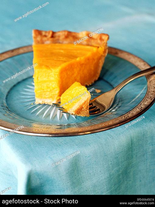 A slice of pumpkin pie with piece on fork