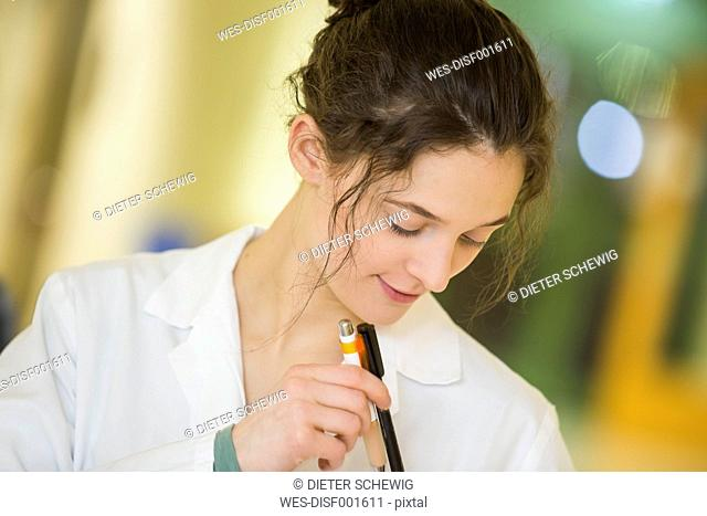 Smiling teenage girl in doctor's overall with ballpen