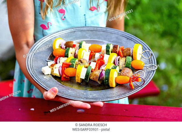 Girl holding plate with vegetarian grill skewers, tomato, yellow and green zucchini, tofu, feta, onion and champignon