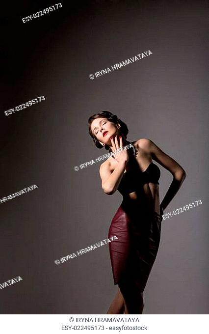 Femininity. Elegant Daydreaming Woman posing in Studio over Grey Background