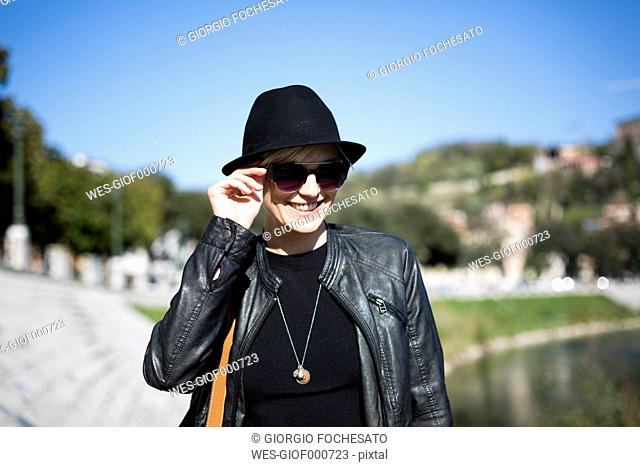 Portrait of smiling blond woman wearing sunglasses, hat and leather jacket