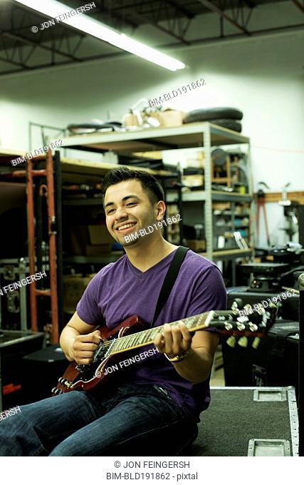 Hispanic man playing guitar in warehouse