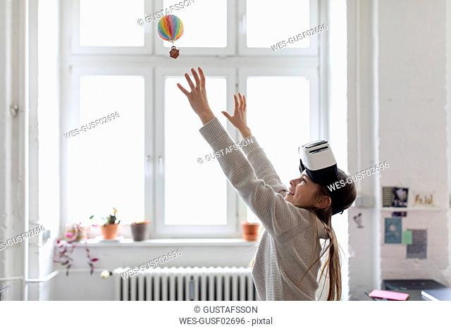Girl with VR glasses trying to catch hot-air balloon in office