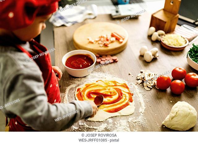 Little boy preparing pizza at home