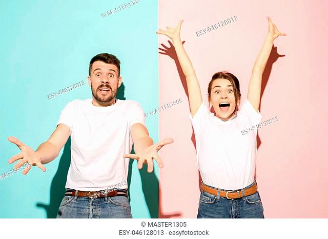 Closeup portrait of young couple, man, woman. One being excited happy smiling, other serious, concerned, unhappy at studio. Emotion contrasts concept