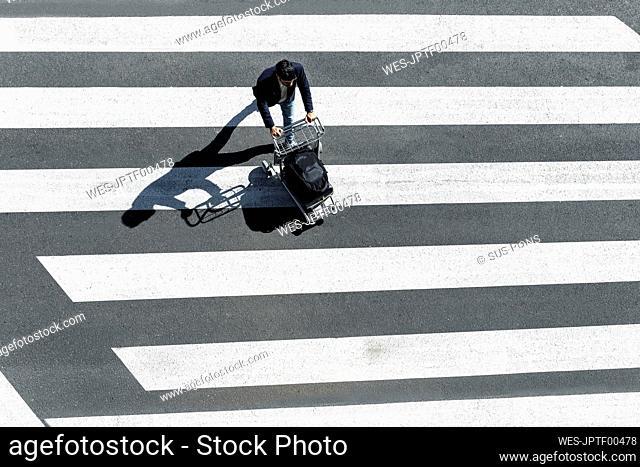 Man on zebra crossing pushing baggage cart, top view