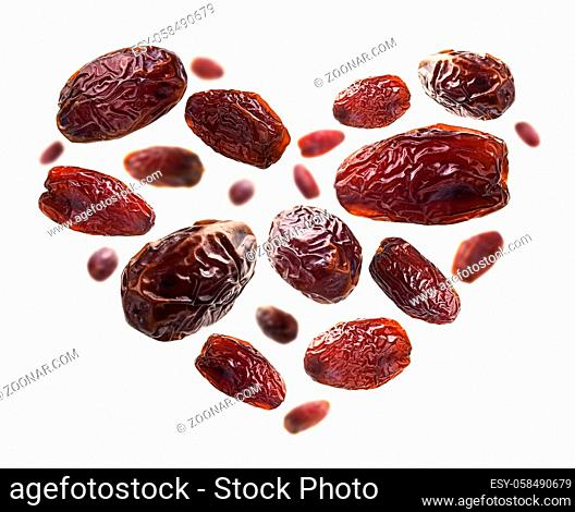 Dried dates in the shape of a heart on a white background