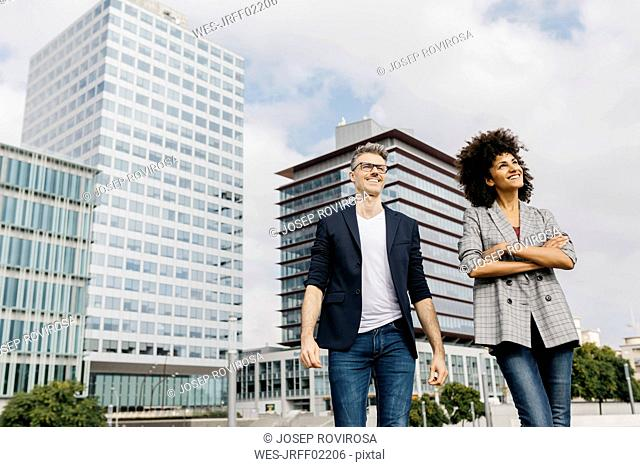 Two happy colleagues walking outside office building
