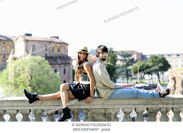 Happy young couple sitting back to back on balustrade