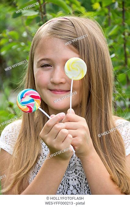 Portrait of girl holding lollipops