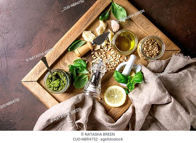 Traditional Basil pesto sauce in glass jar with ingredients above fresh basil, olive oil, parmesan cheese, garlic, pine nuts