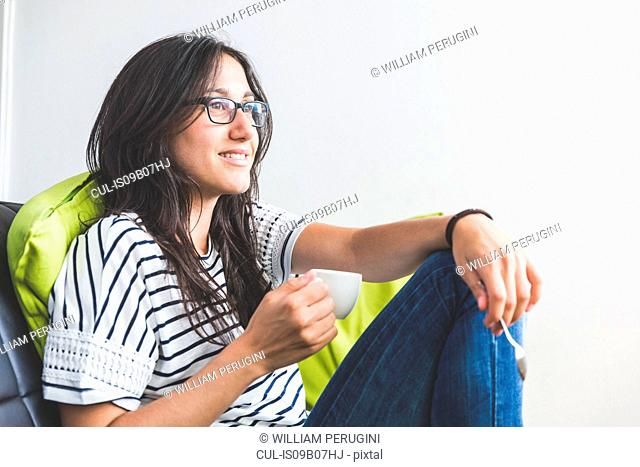 Woman sitting on sofa holding coffee cup smiling