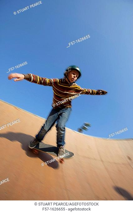 Young teenager skateboarding in a bowl