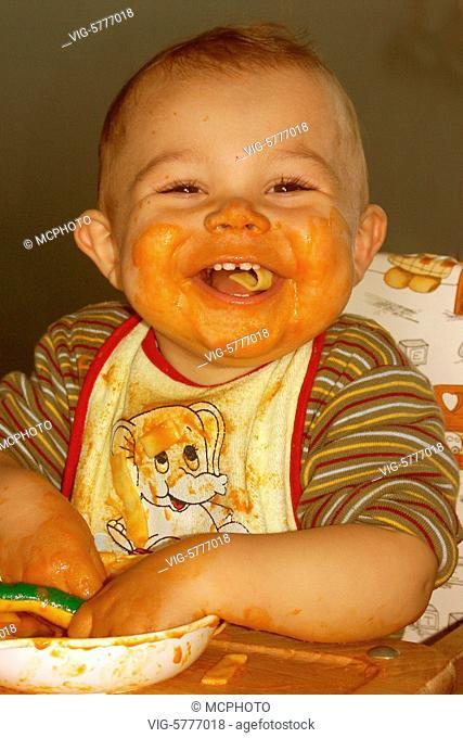 Baby isst Nudeln mit Tomatensauce und ist vollkommen vollgeschmiert - Germany, 15/09/2005