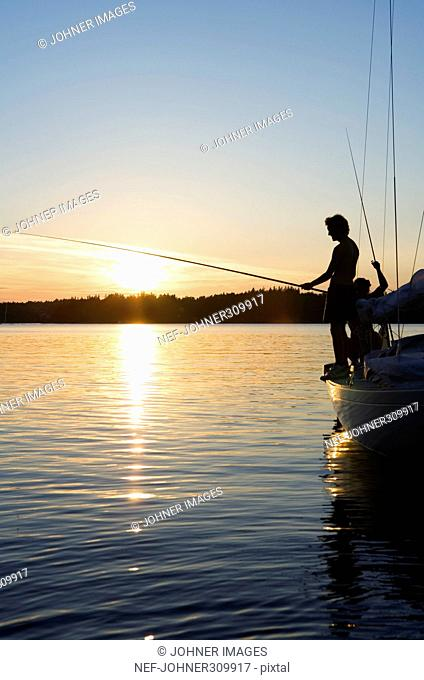 Two men fishing from a sailing boat in the sunset