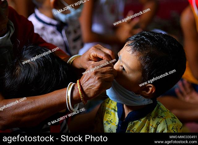AGARTALA, TRIPURA, INDIA, 02-05-2020 :An anganwadi (Anganwadi is a type of rural child care centre in India) worker is adjusting the mask of a child