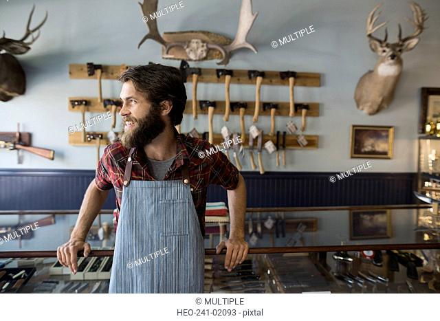 Smiling bearded shop worker looking away