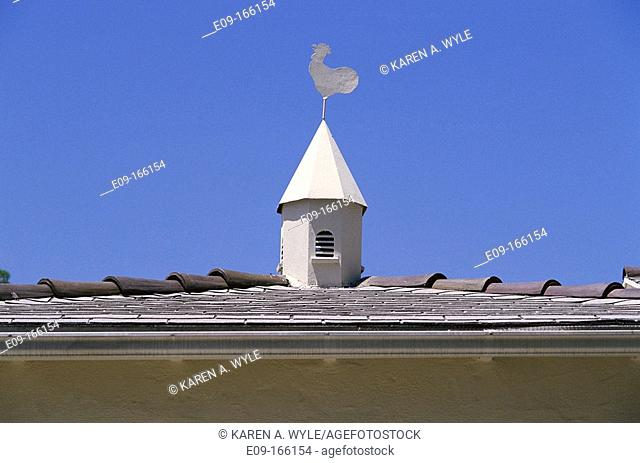 White rooster weathervane atop small white towerlike feature on tile roof, against blue sky. Los Angeles. California. USA
