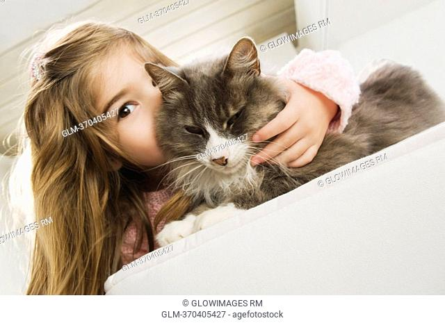 Portrait of a girl kissing a cat
