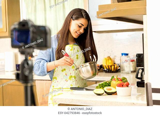 Cute young woman beating some eggs and recording a cooking video for her blog
