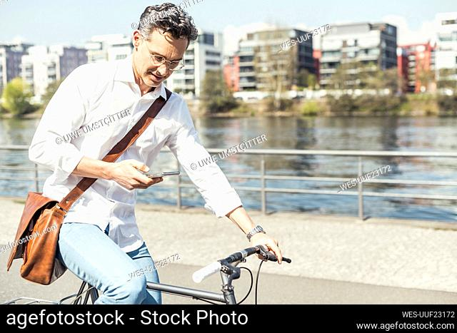 Businessman using mobile phone while cycling bicycle on sunny day