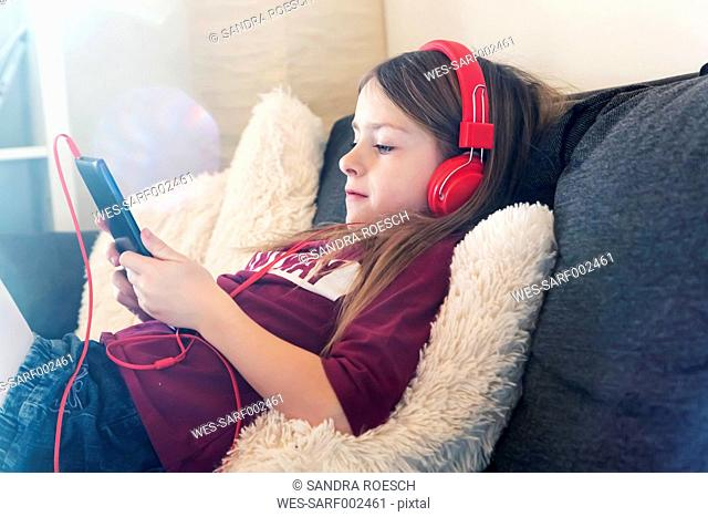 Girl sitting on the couch listening music with headphones and digital tablet