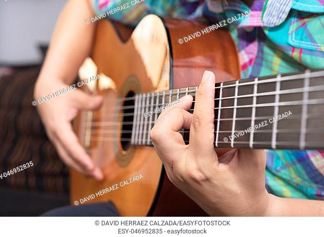 Bearded hipster man hand playing acoustic guitar. Close-up selective focus on hand