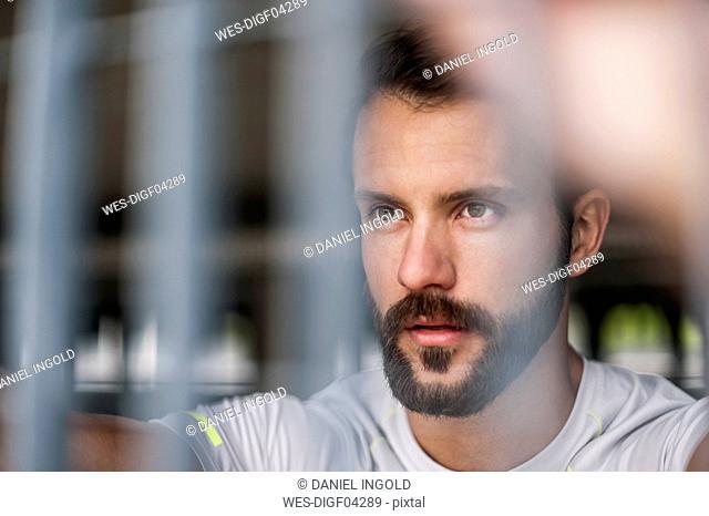 Portrait of confident athlete behind grid