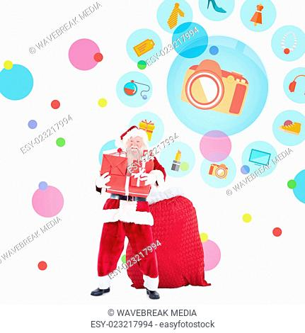 Composite image of santa holding pile of gifts