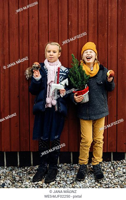 Girl and laughing boy standing in front of wooden wall with toy horse and chocolate dipped apple