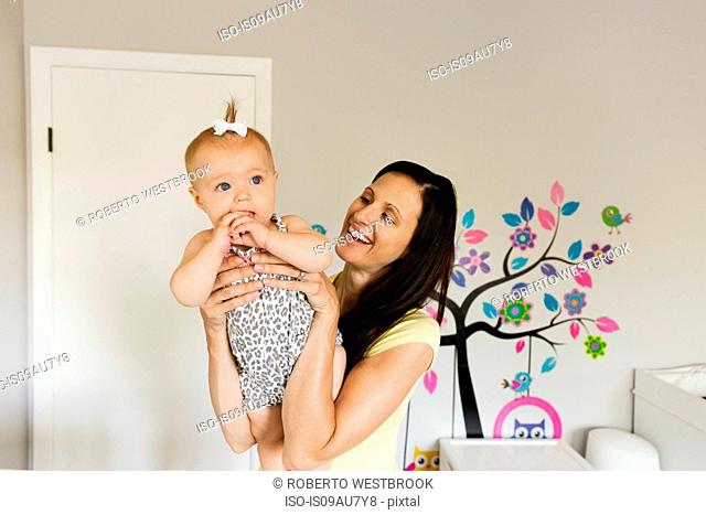 Happy mid adult mother holding up baby daughter