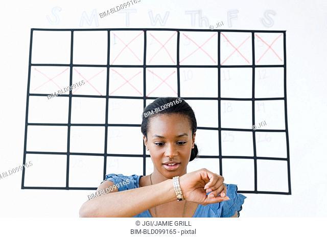 Black woman checking her wristwatch