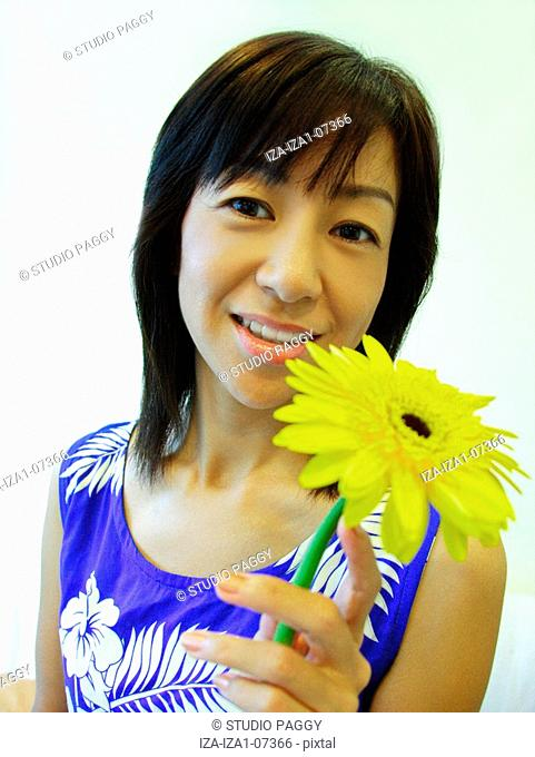 Portrait of a mid adult woman holding a Gerbera Daisy flower and smiling