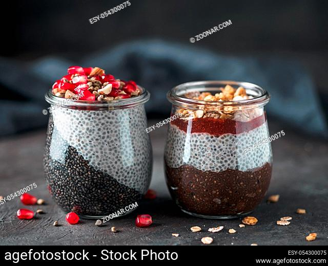 Two chia pudding in glass jars on dark table. Two colors charcoal chia puding with pomegranate, almond, hemp seeds. Chocolate chia pudding with jam and granola