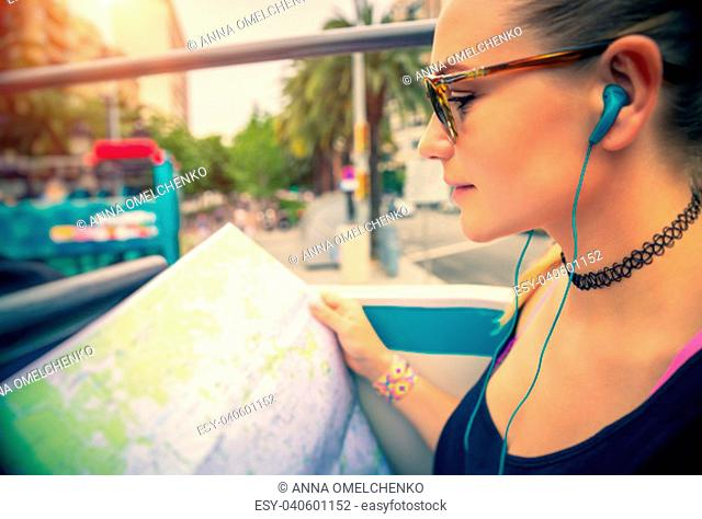 Pretty girl enjoying bus tour to Europe, exploring map and listening guides stories about famous places of Barcelona, happy active summer vacation